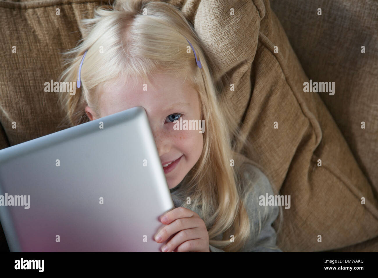 A young girl holding a silver laptop in front of her face. - Stock Image