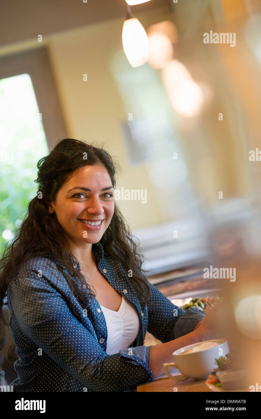 A woman seated in a cafe - Stock Image