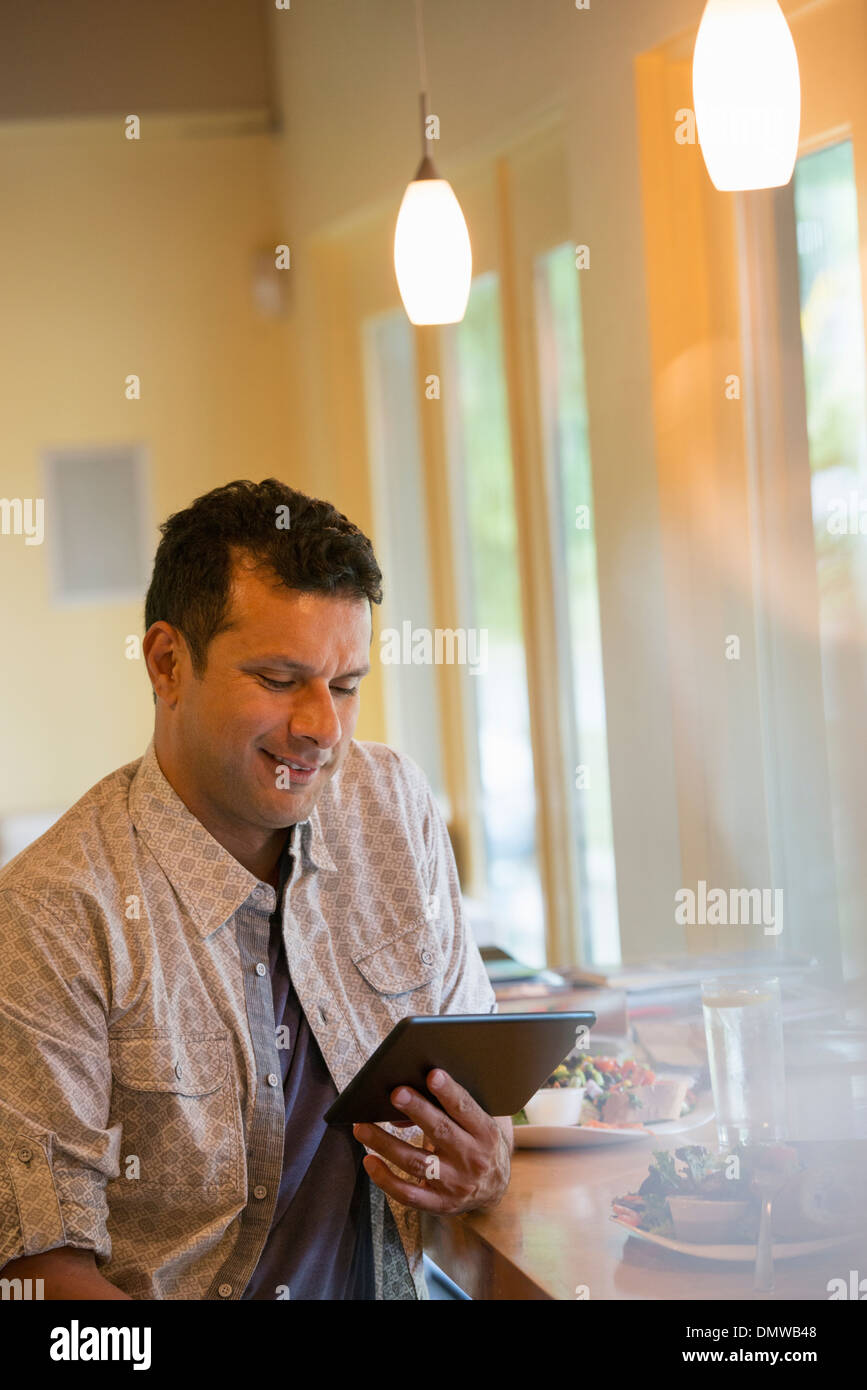 A man using a digital tablet. - Stock Image