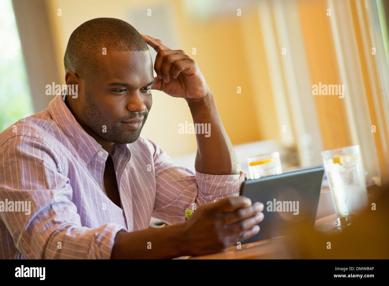 A man in a cafe using a digital tablet. - Stock Image