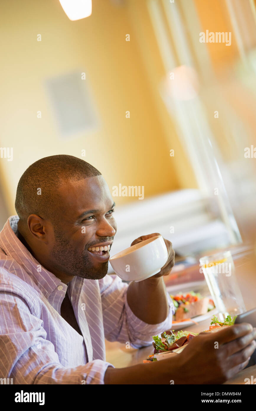 A man in a cafe holding a cup of coffee. - Stock Image