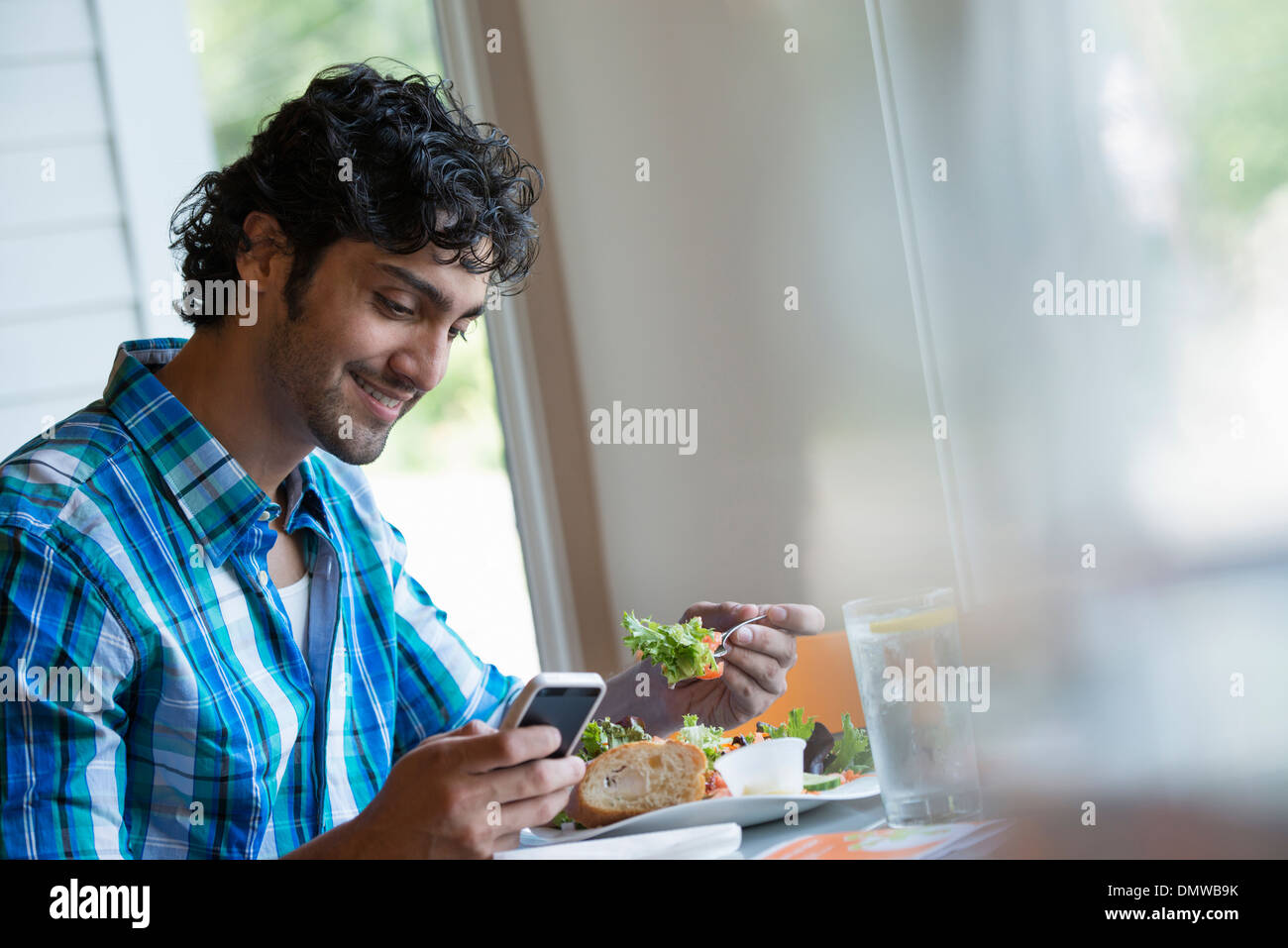 A  man seated checking his phone and eating in a cafe. - Stock Image