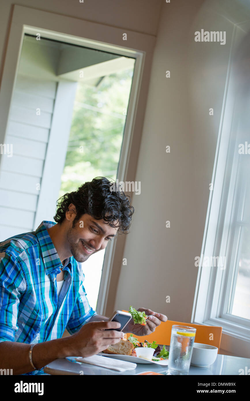 A man checking his phone at a cafe table. - Stock Image