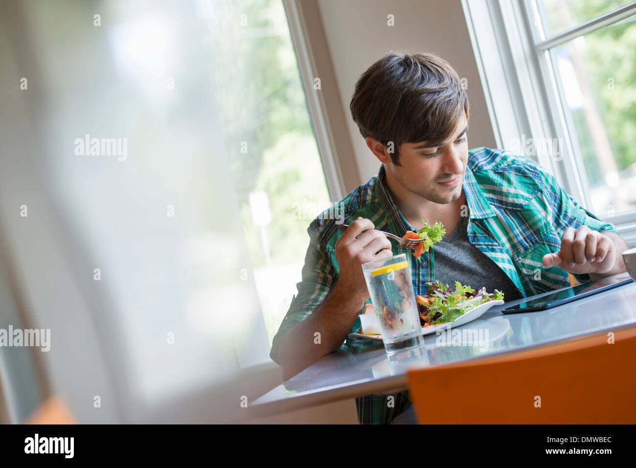 A young man using a digital tablet. - Stock Image