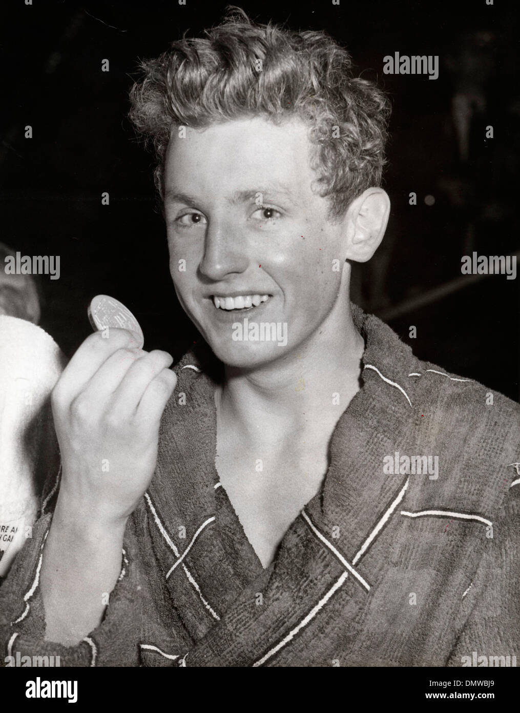July 25, 1958 - London, England, U.K. - Scottish IAN BLACK was a champion swimmer as well as BBC Sports Personality of the Year. PICTURED: Black proudly displays his gold medal after he had won the 220 yards Butterfly swim at the Empire Pool last night. His time 2min. 22.6 secs. was only 2.6secs outside the world record.  (Credit Image: © KEYSTONE Pictures USA/ZUMAPRESS.com) - Stock Image