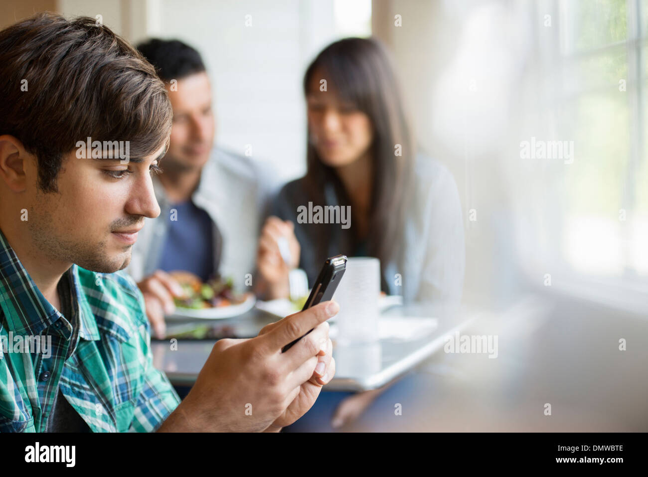 Three people seated at a cafe table. - Stock Image