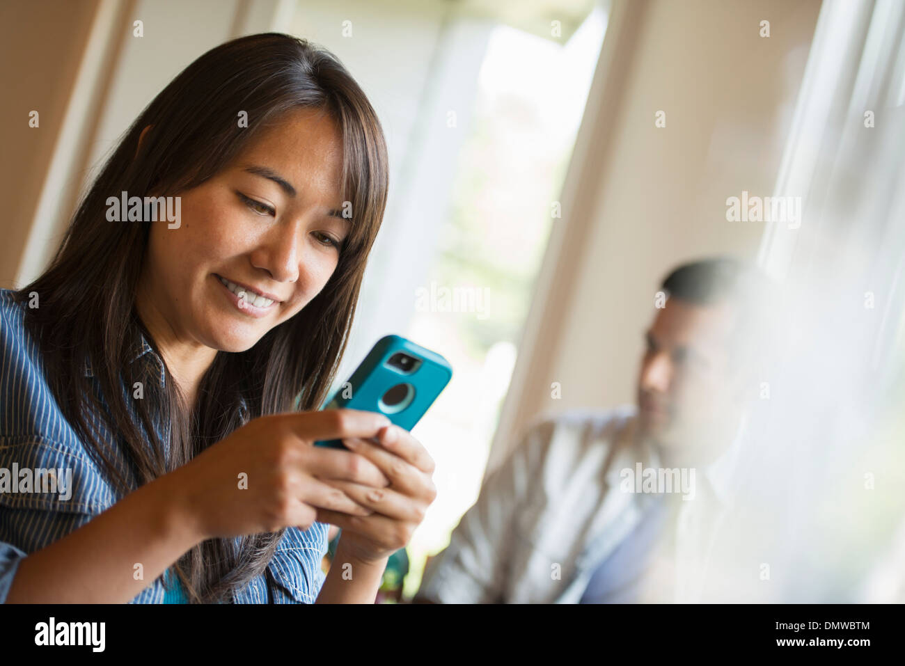 A woman checking her smart phone in a cafe. - Stock Image