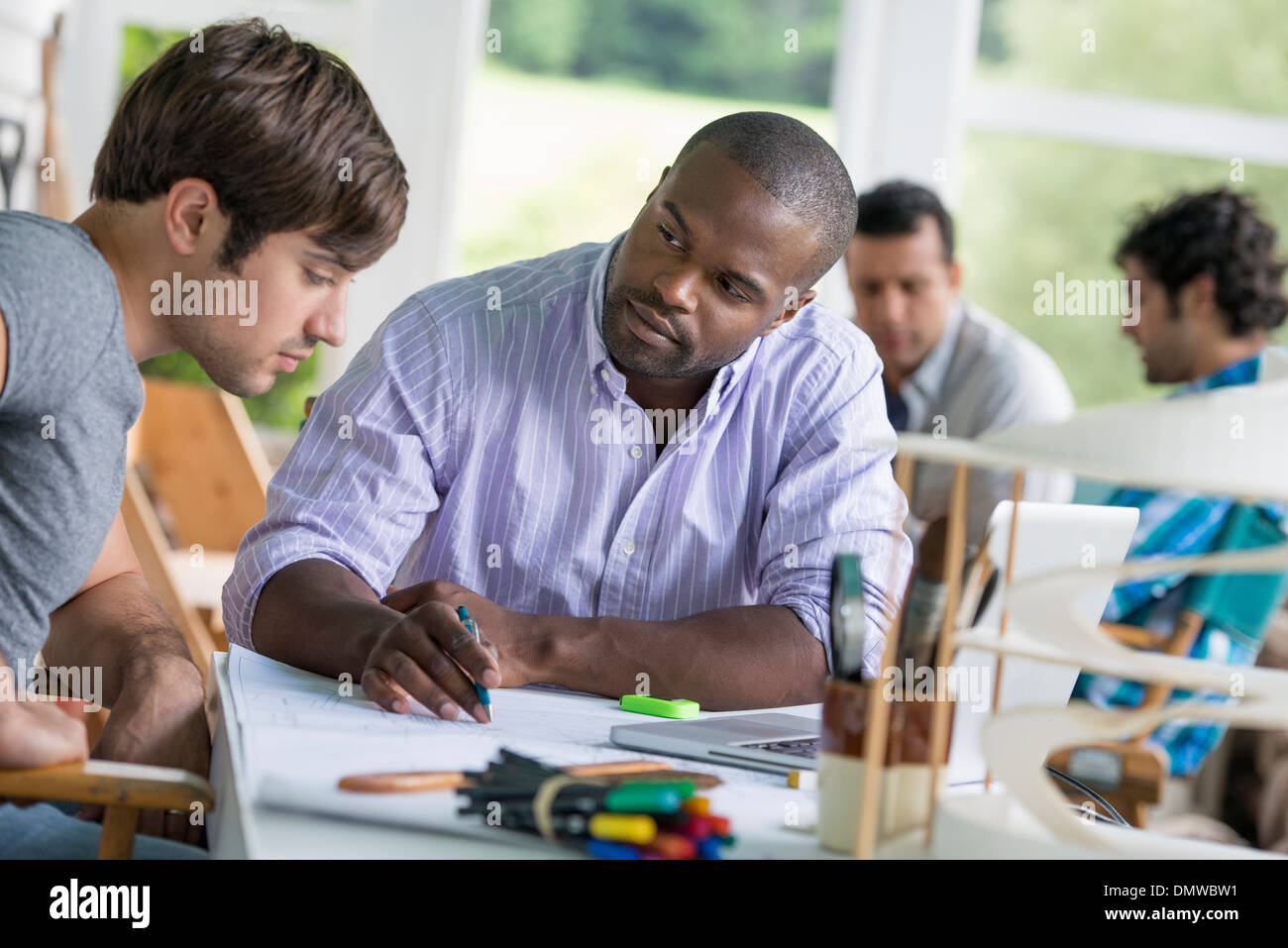 Two men seated one drawing on paper - Stock Image