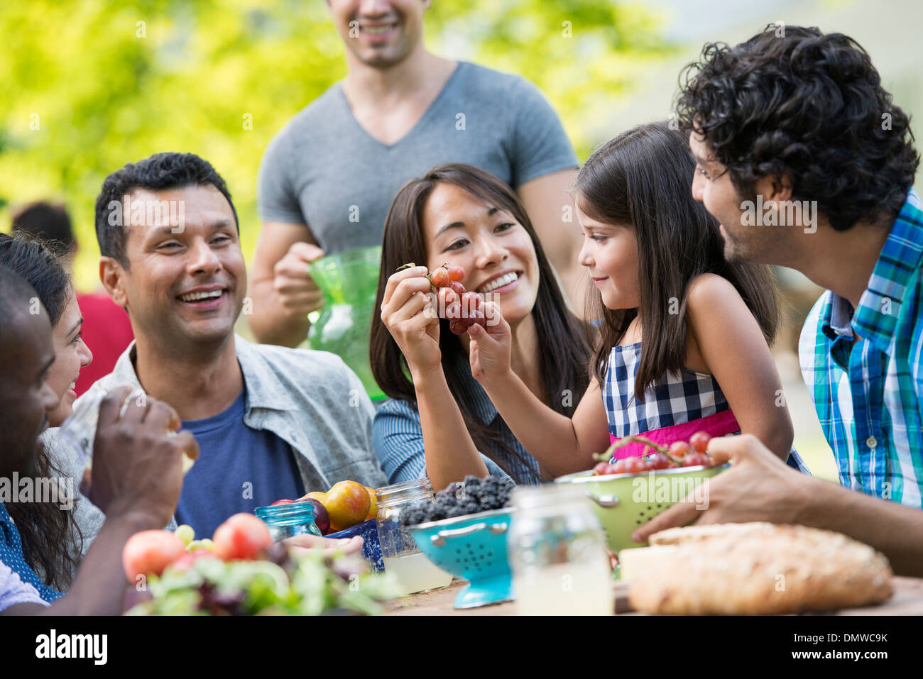 Adults and children around a table in a garden. - Stock Image