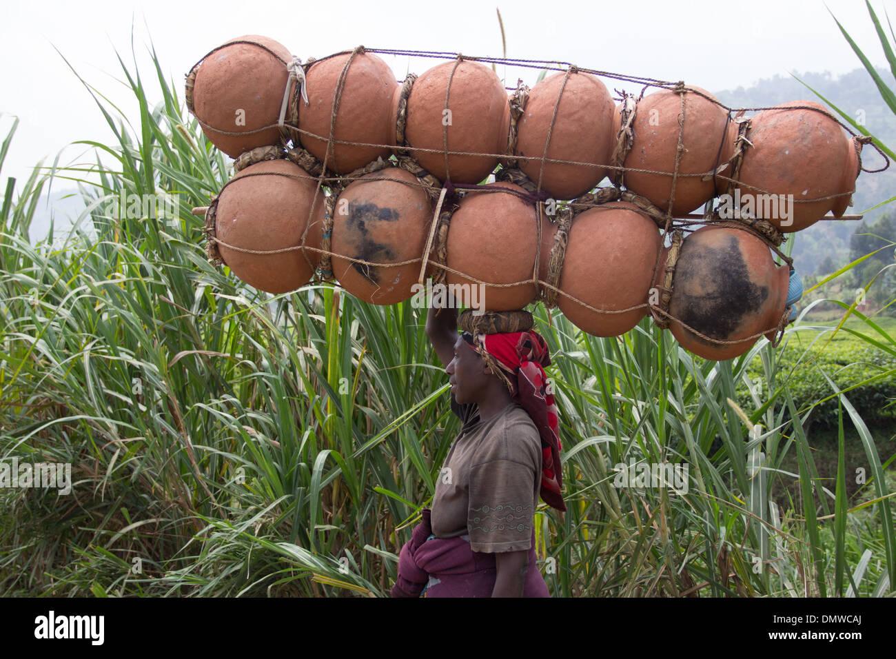 black woman carrying bottles burden bearer - Stock Image