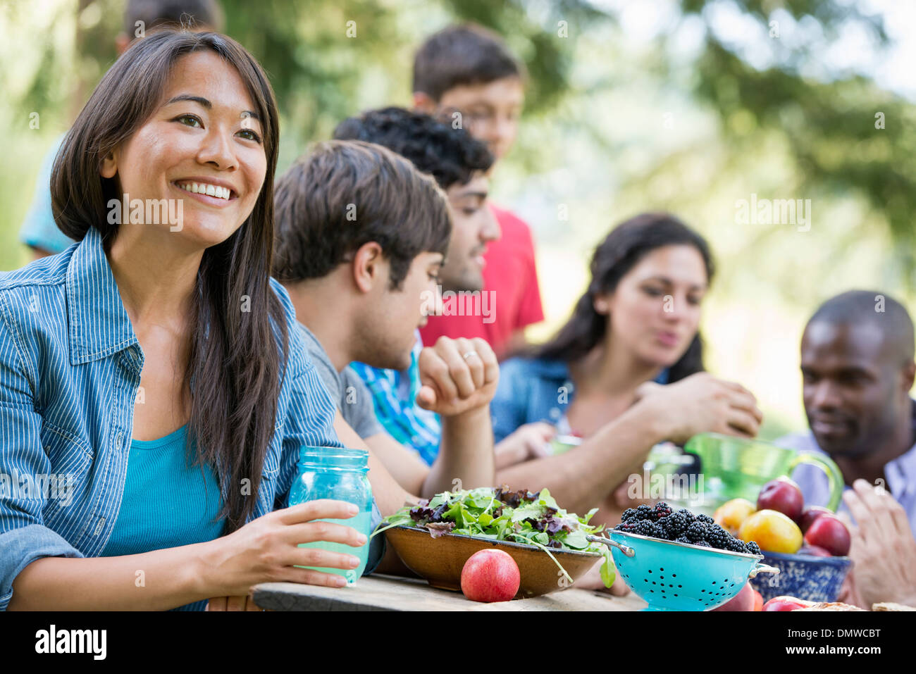 Adults and children around a table at a party in a garden. - Stock Image