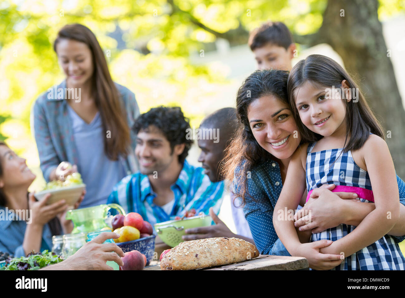 A summer party outdoors. Adults and children smiling and looking at  camera. - Stock Image