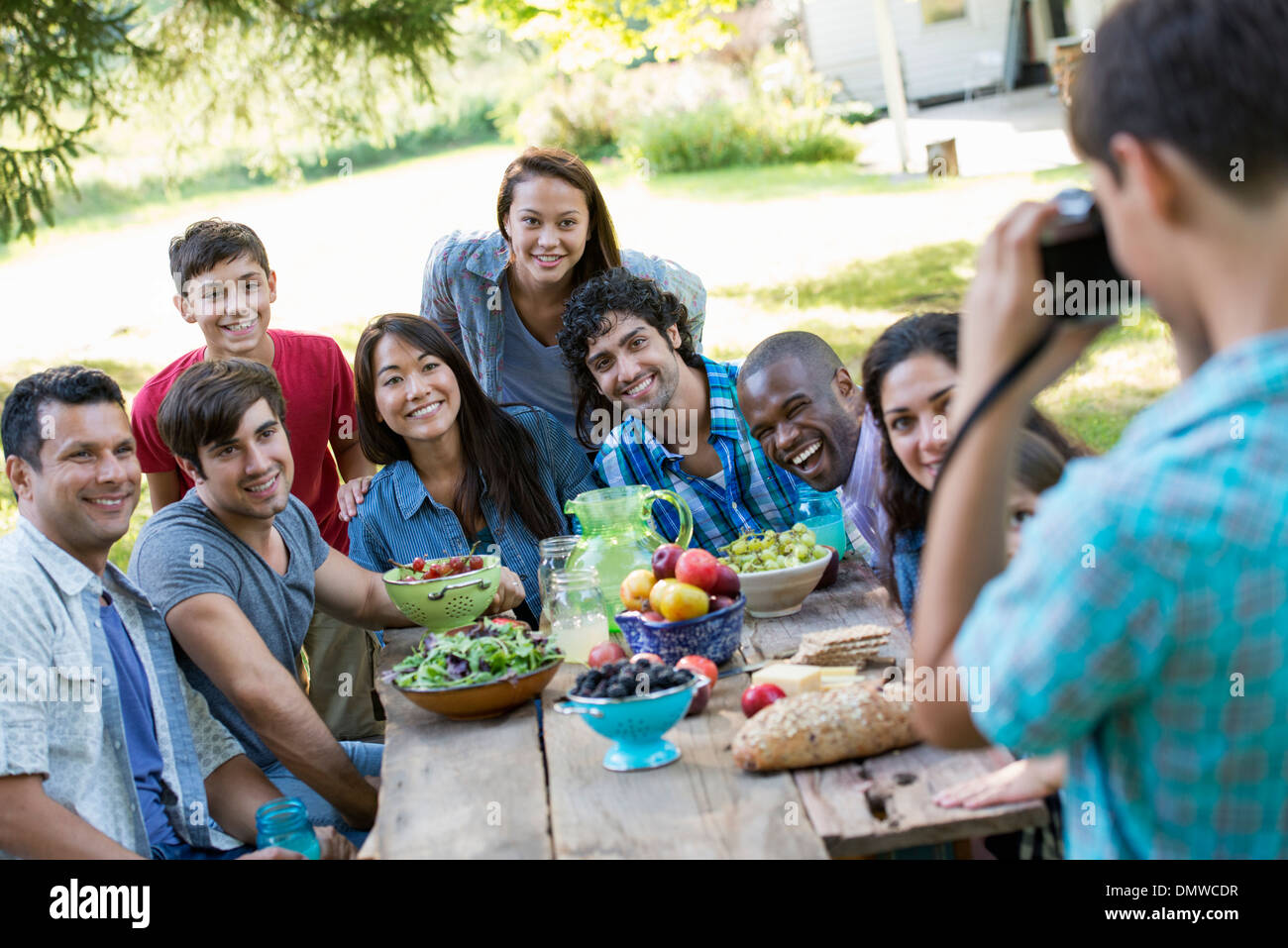 A summer party outdoors. Adults and children posing for a photograph. - Stock Image