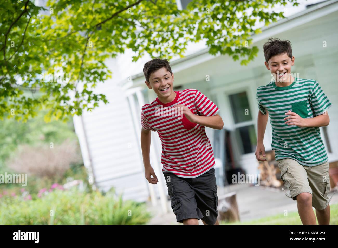 Two boys in a farmhouse garden in summer. - Stock Image