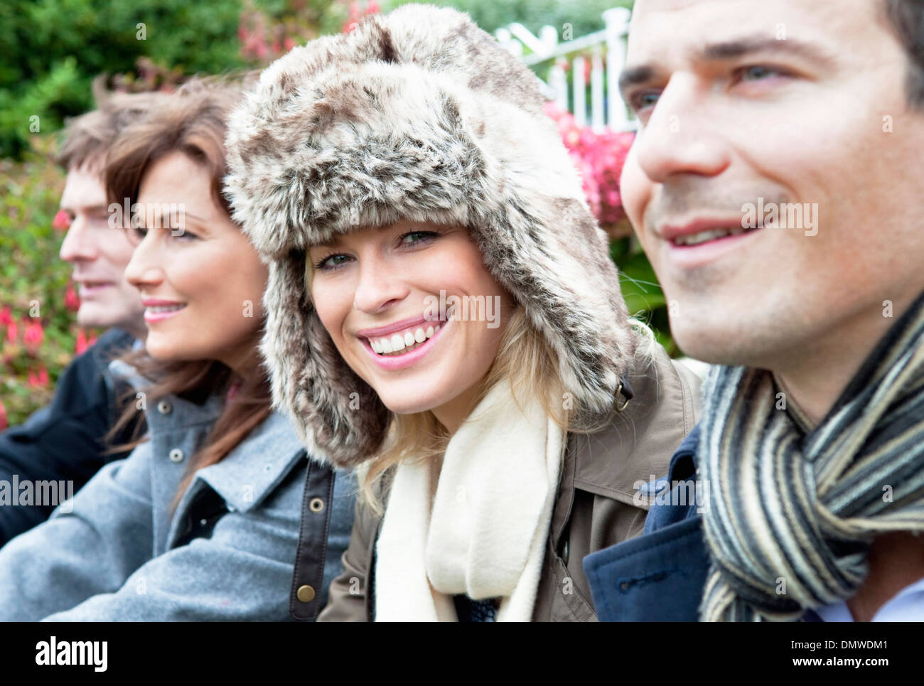 Four people outdoors in coats and scarves. - Stock Image