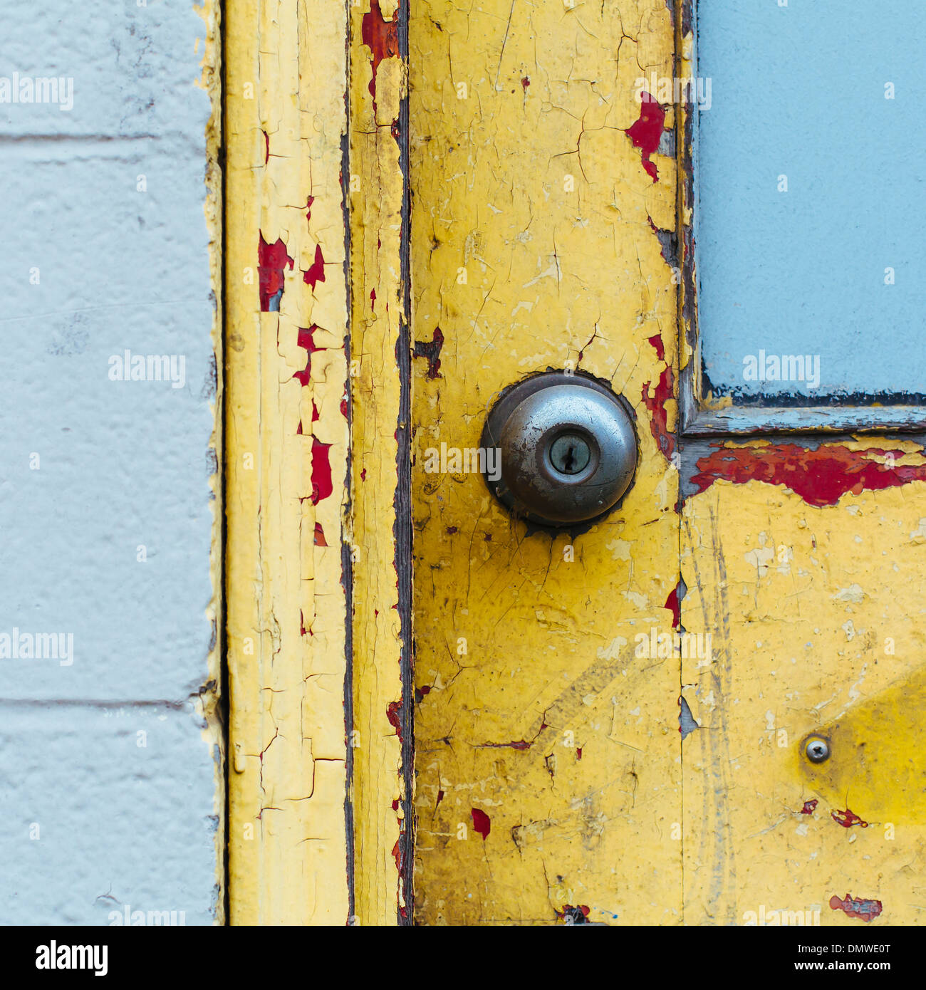 A doorway and  doorbell of a building. Flaked damaged paint. - Stock Image