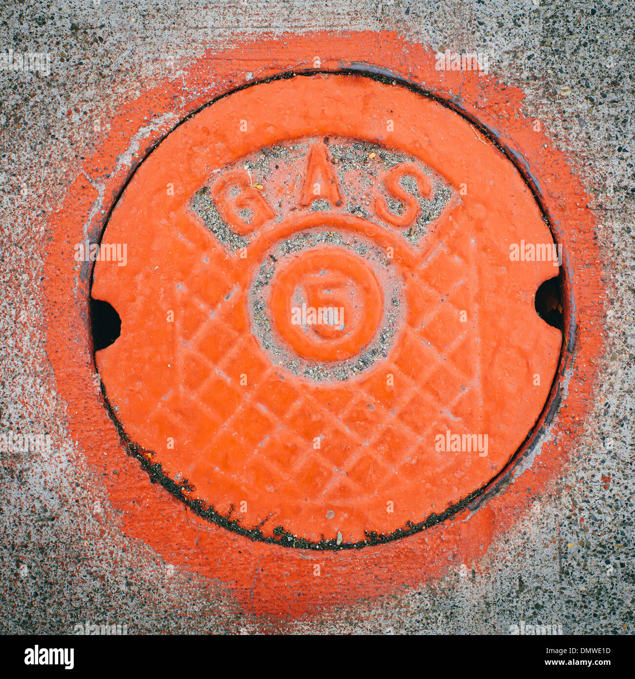 A gas manhole cover round and painted orange on  road in Seattle. - Stock Image