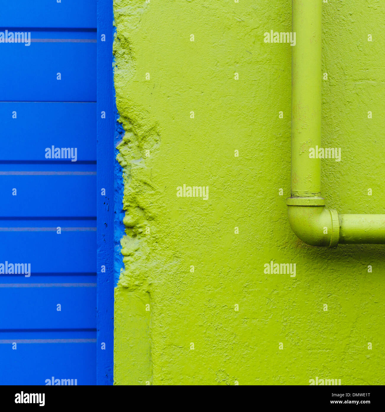 A green painted wall and pipe by a blue doorway. - Stock Image