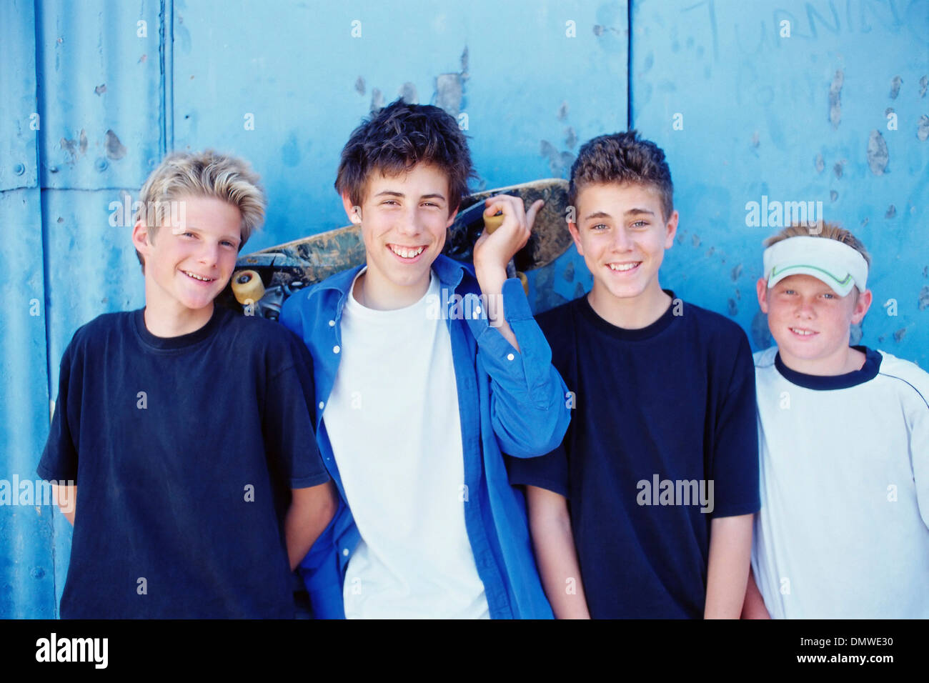 Four young boys in a row friends skateboarding. - Stock Image