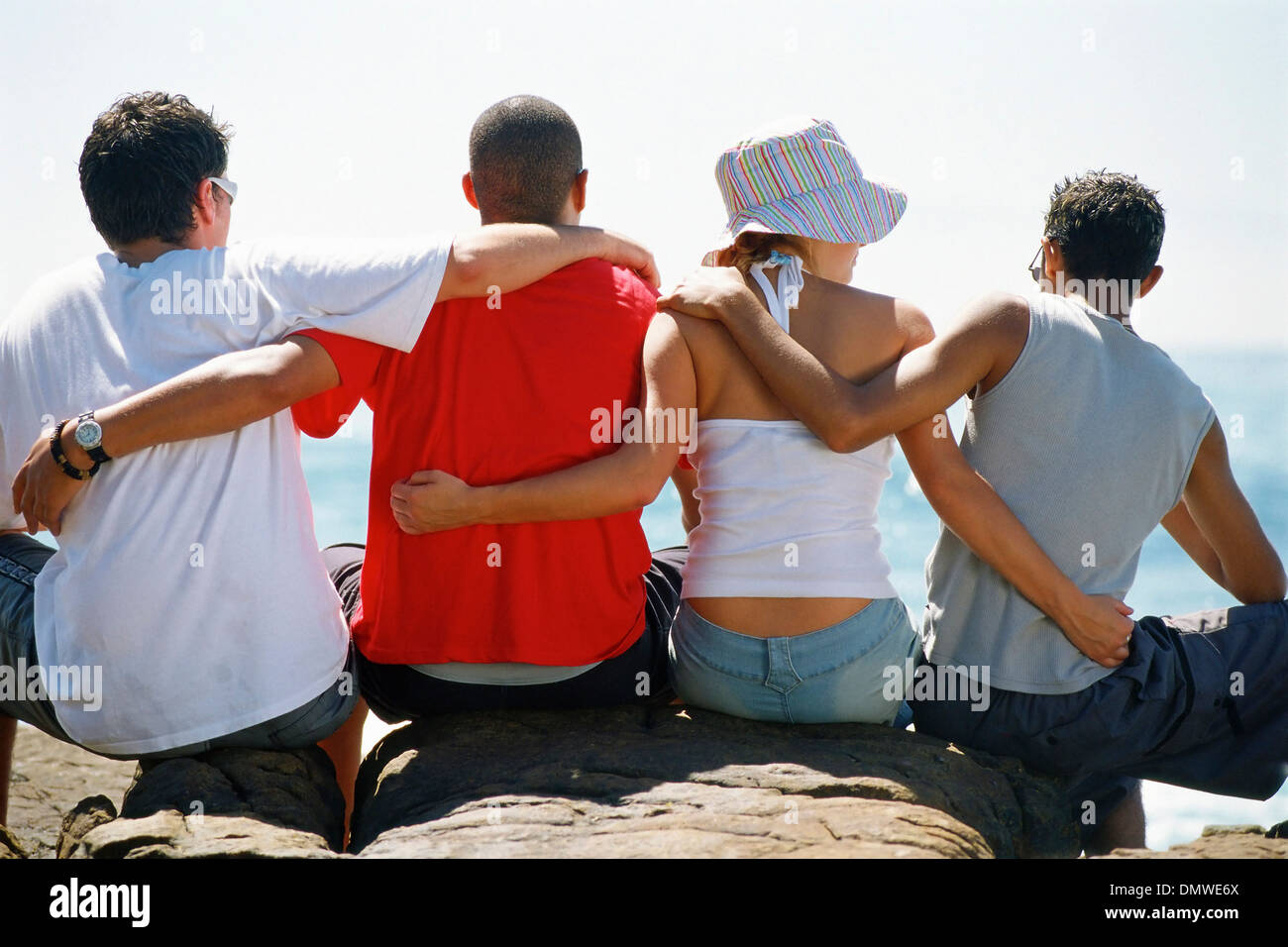 Back view of four friends with arms around each or sitting in a row. - Stock Image