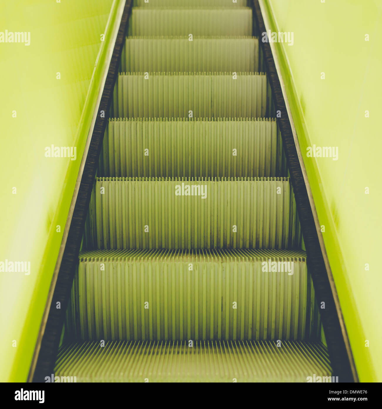 A flight of steps an escalator with a yellow painted border stripe on each side. - Stock Image