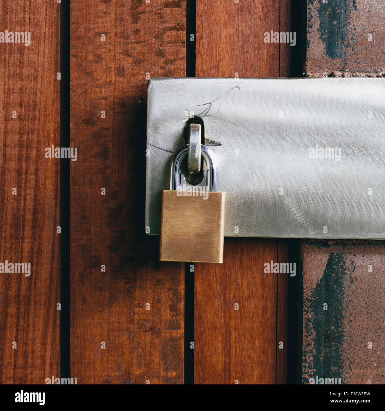 Close up of a wooden doorway with a padlock. - Stock Image