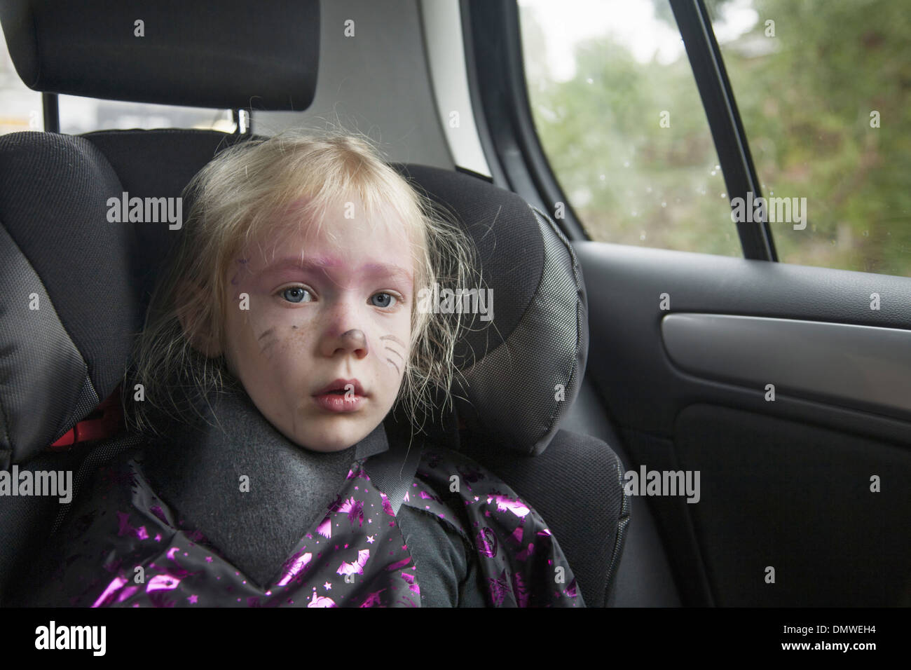 A young girl in a car seat in Halloween costume. - Stock Image