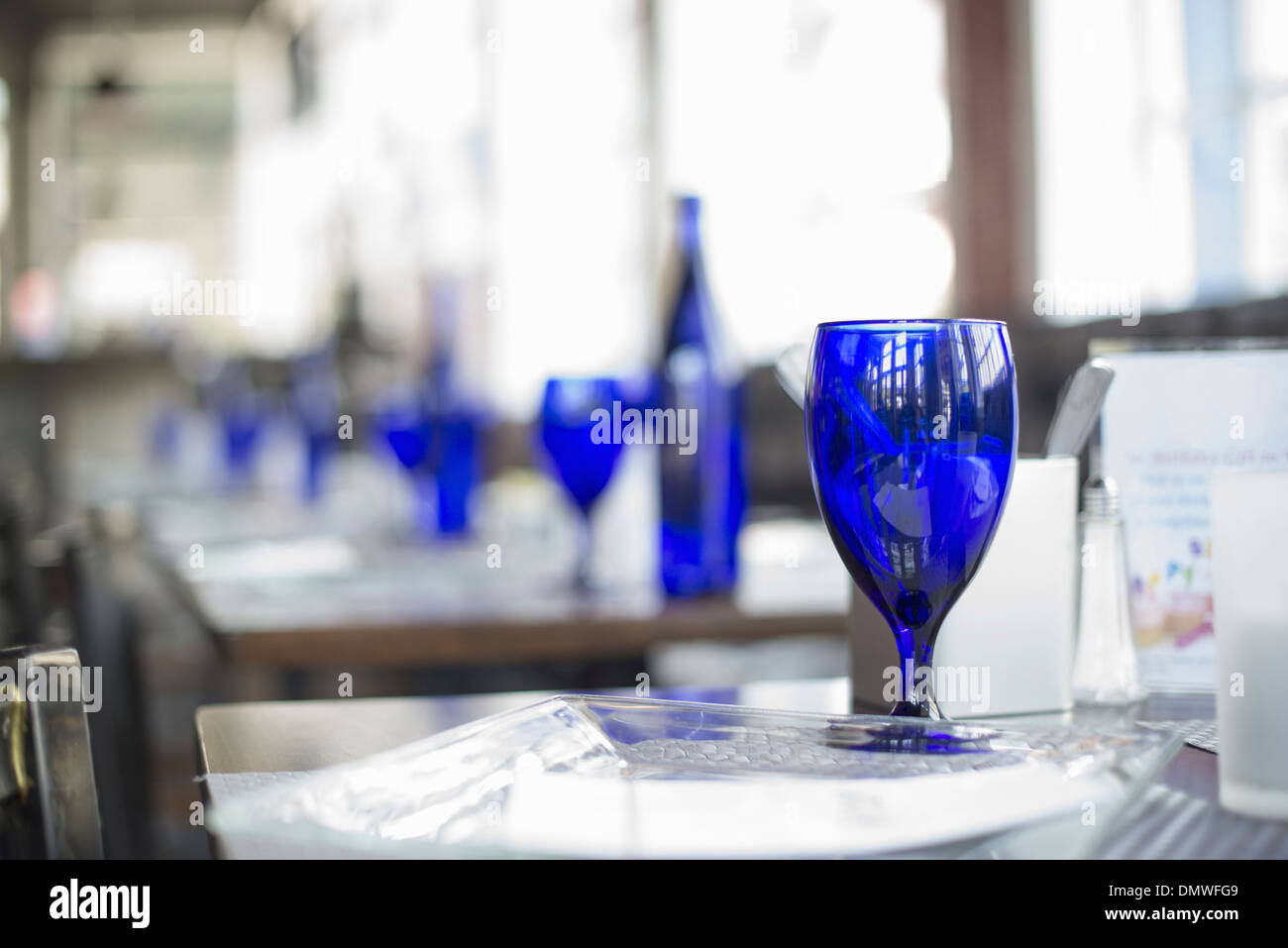 A cafe interior. Bright blue glassware on empty tables. - Stock Image