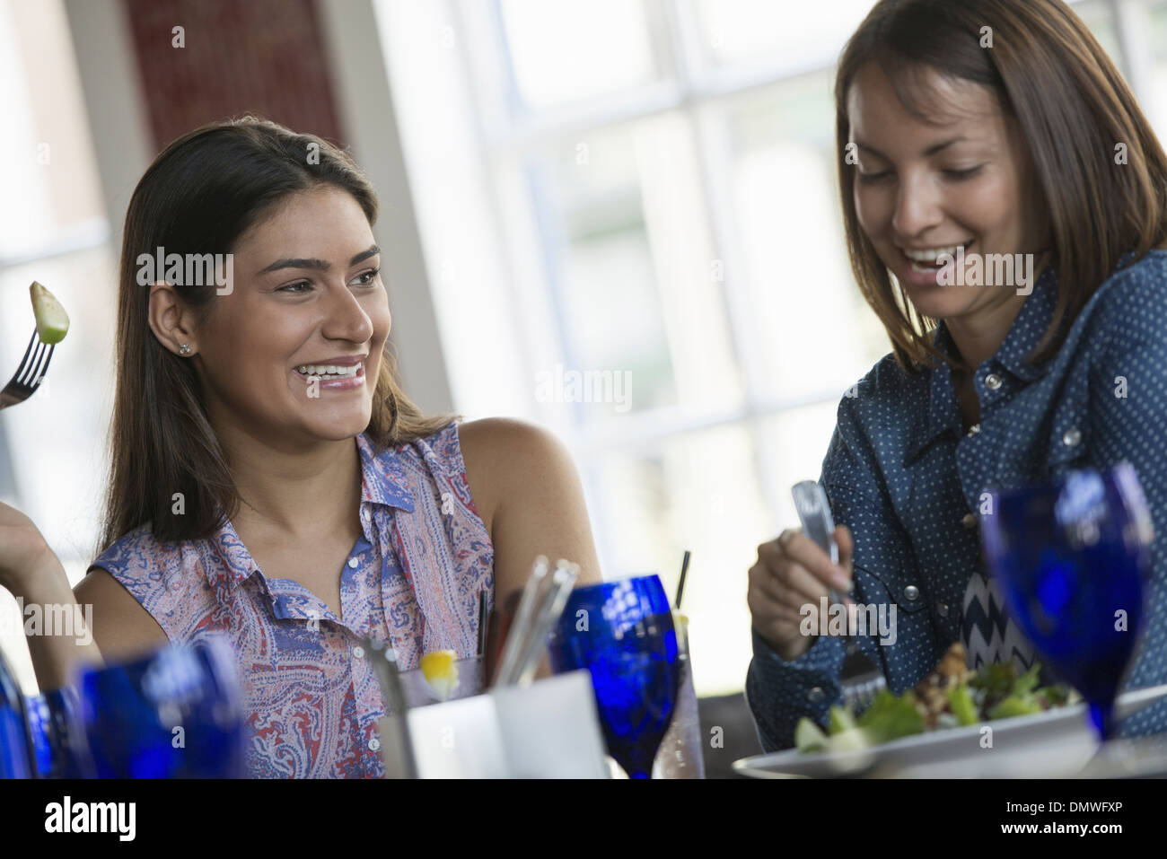 Two women seated at a cafe table having a meal. - Stock Image