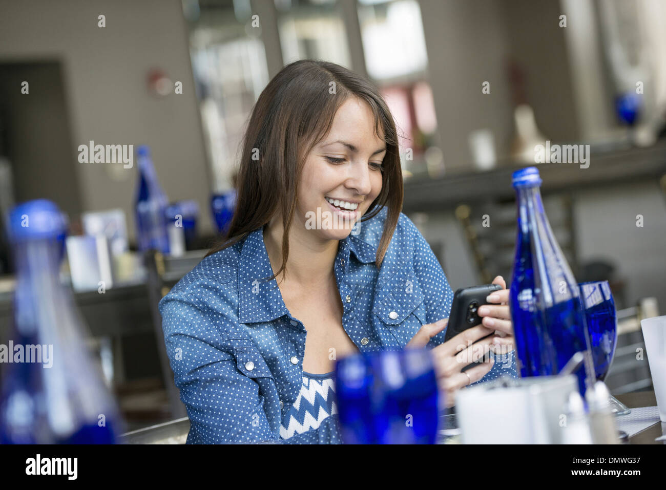 A woman seated in a cafe using a smart phone. - Stock Image