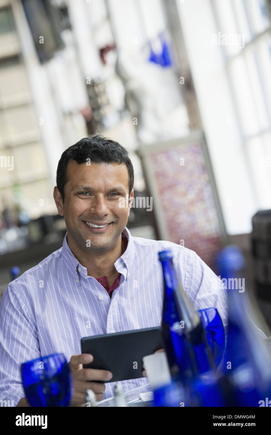 A cafe interior. A man sitting using a digital tablet. Stock Photo