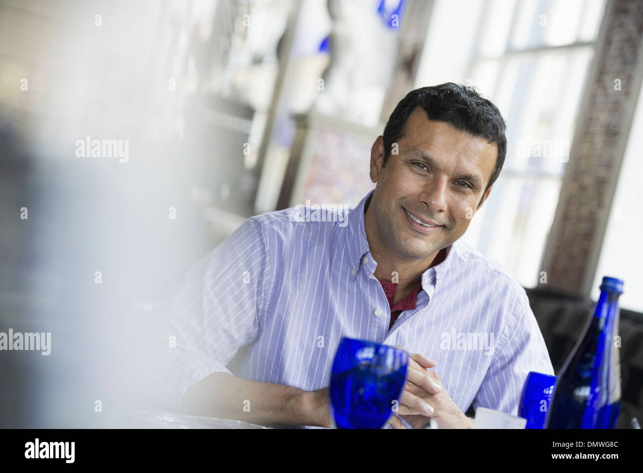 A cafe interior. A man seated at a table. - Stock Image