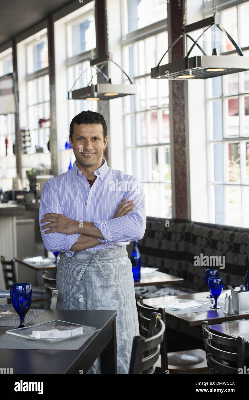 A cafe interior. A man in chef's whites. - Stock Image
