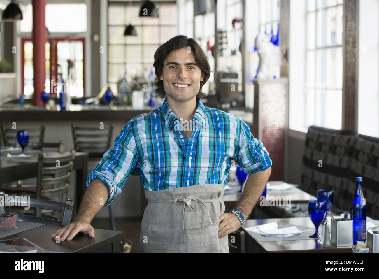 A cafe interior. A waiter in a checked shirt. - Stock Image