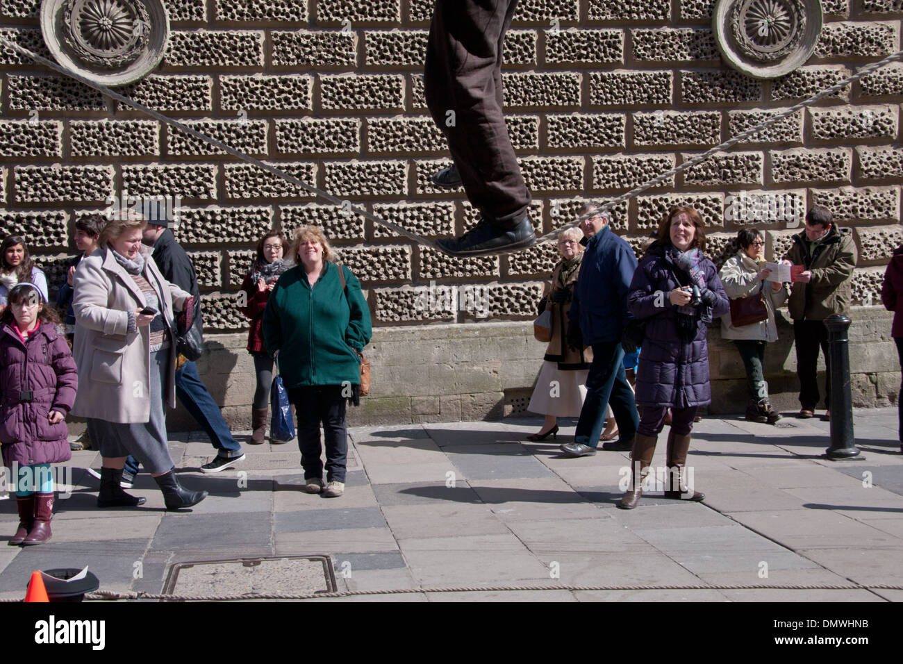 A tightrope walker and pedestrians in Stall Street, Bath - Stock Image