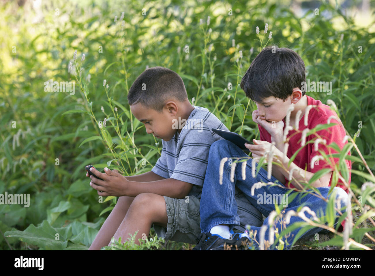 Two boys sitting in a field one on a smart phone and one using a digital tablet. - Stock Image