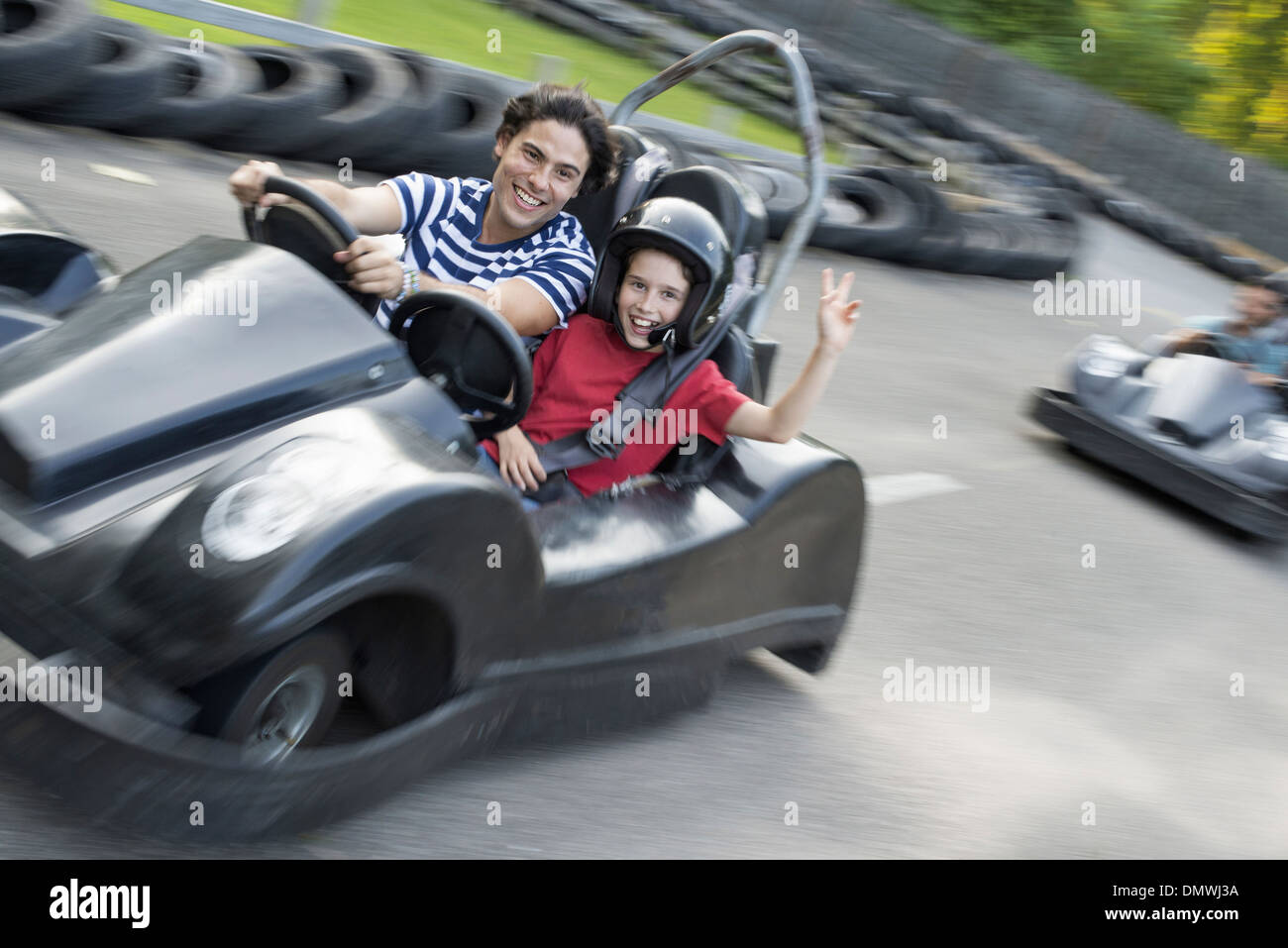 Boys and men go-karting on a track. - Stock Image