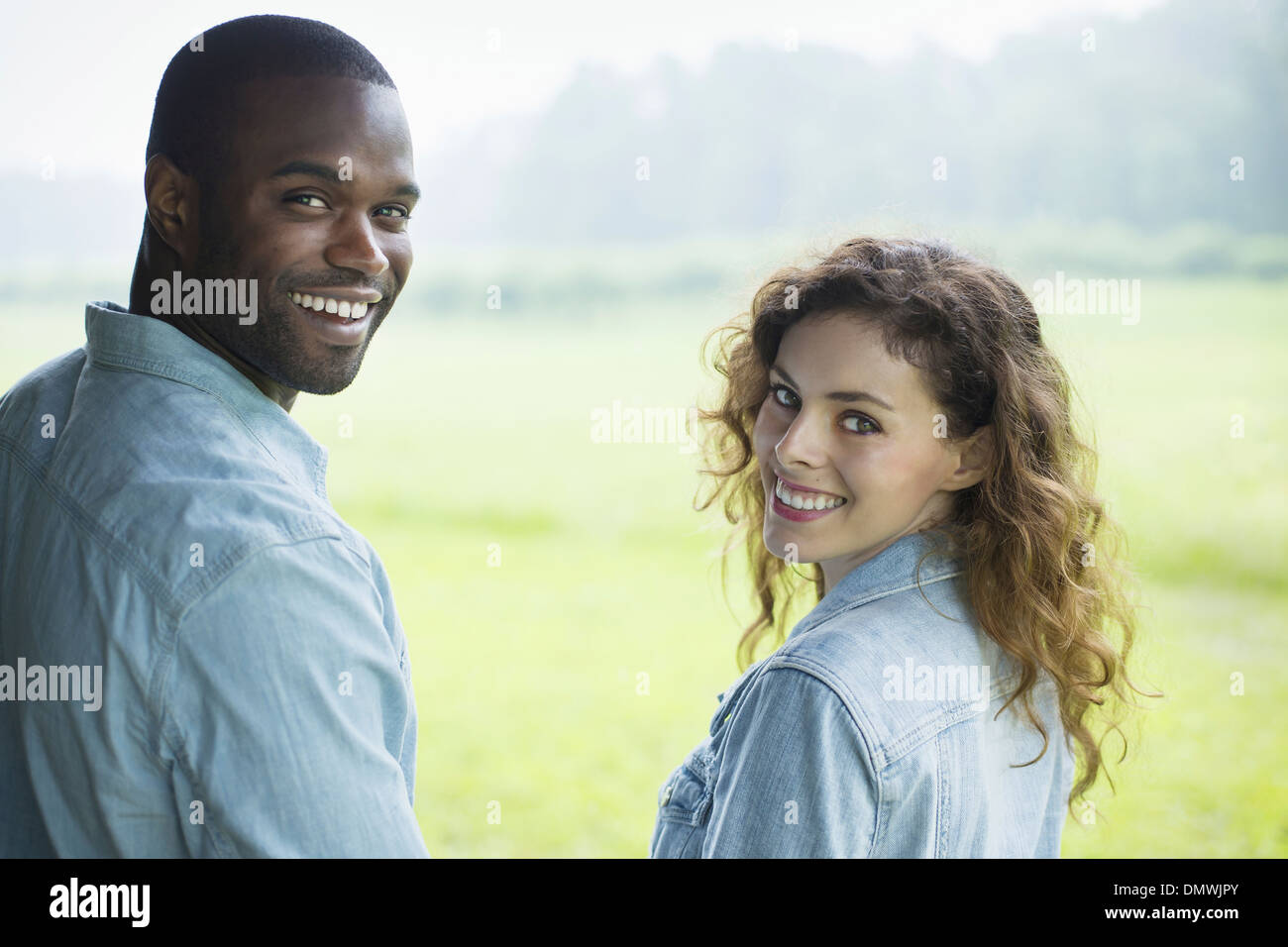 A young man and woman a couple  side by side. Looking over ir shoulders. - Stock Image