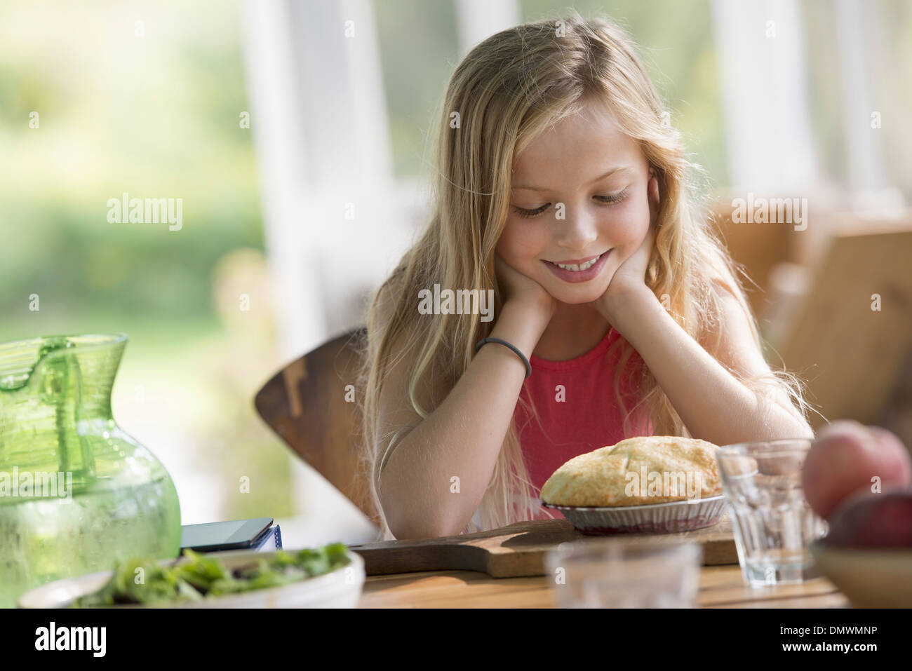 A young girl looking at a pastry pie smiling. - Stock Image