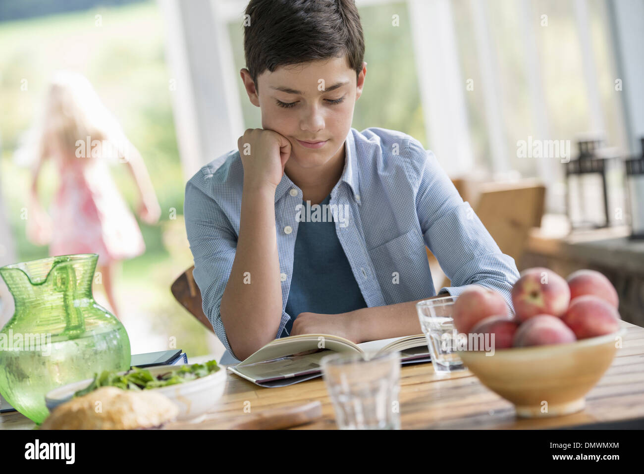 A young boy sitting reading a book. - Stock Image