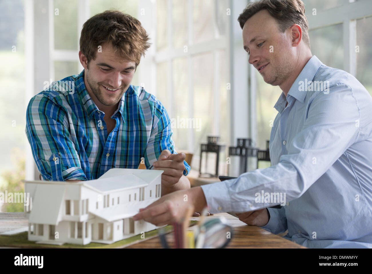 Two men looking at an architectural model of a house. - Stock Image