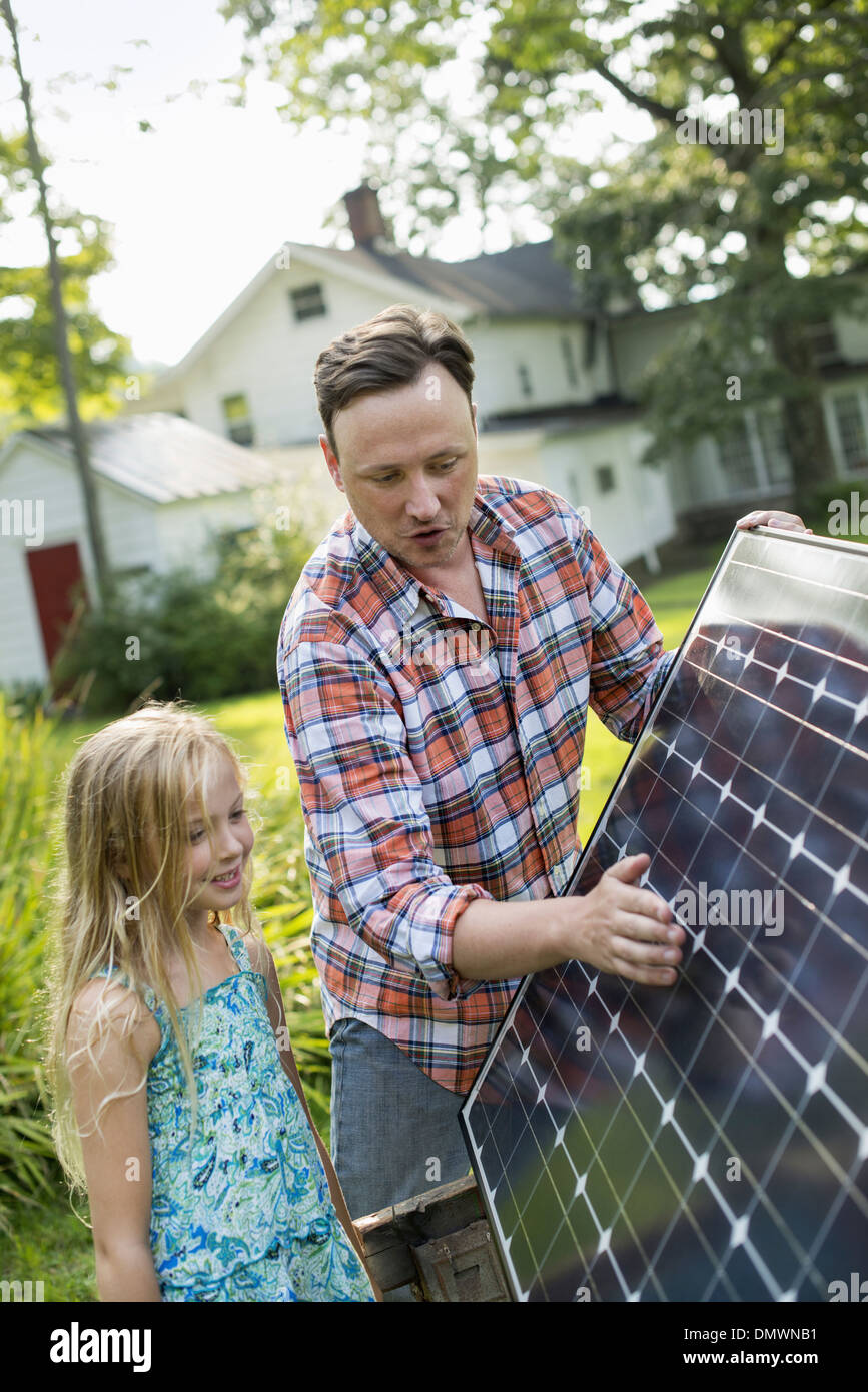 A man and a young girl looking at a solar panel in a garden. - Stock Image