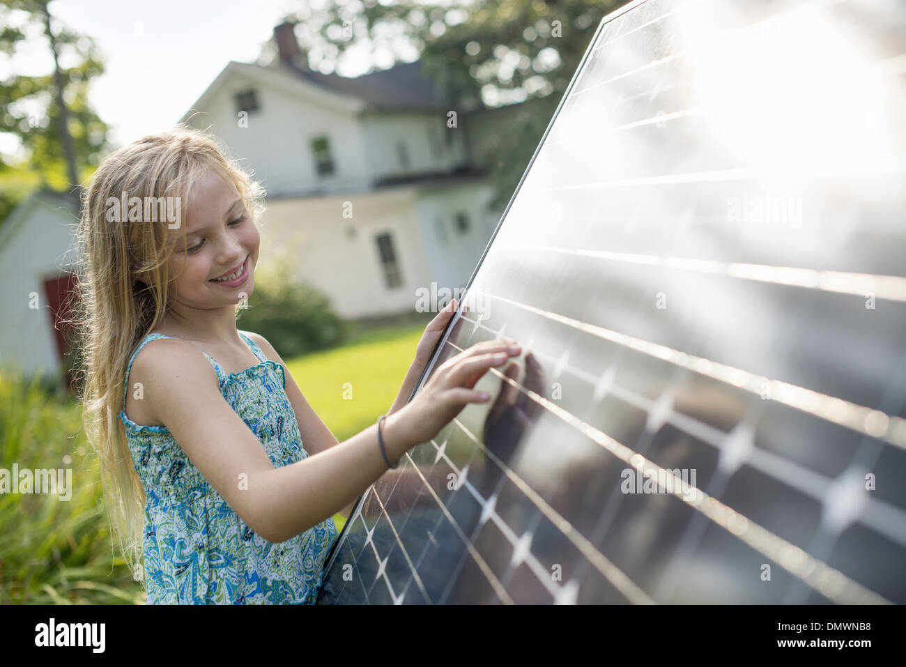 A young girl beside a large solar panel in a farmhouse garden. - Stock Image
