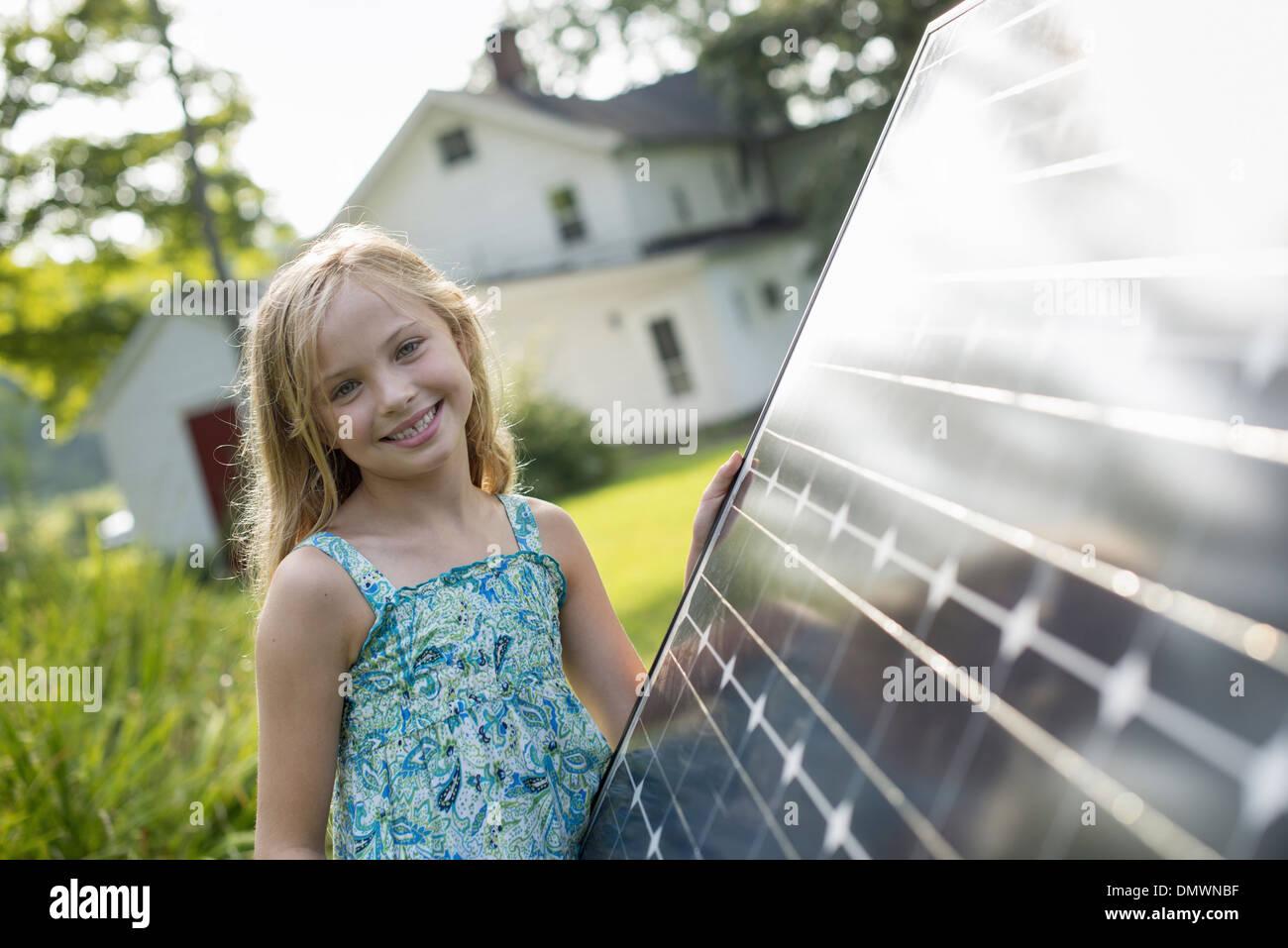 A young girl beside a large solar panel in a farmhouse garden. - Stock Image