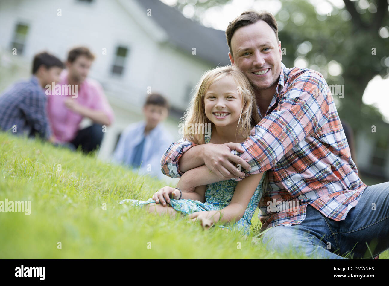 A father and daughter at a summer party sitting on  grass. Stock Photo