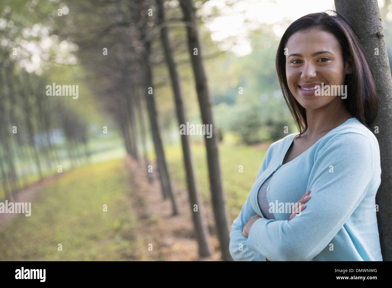 A woman with arms folded leaning against a tree. - Stock Image