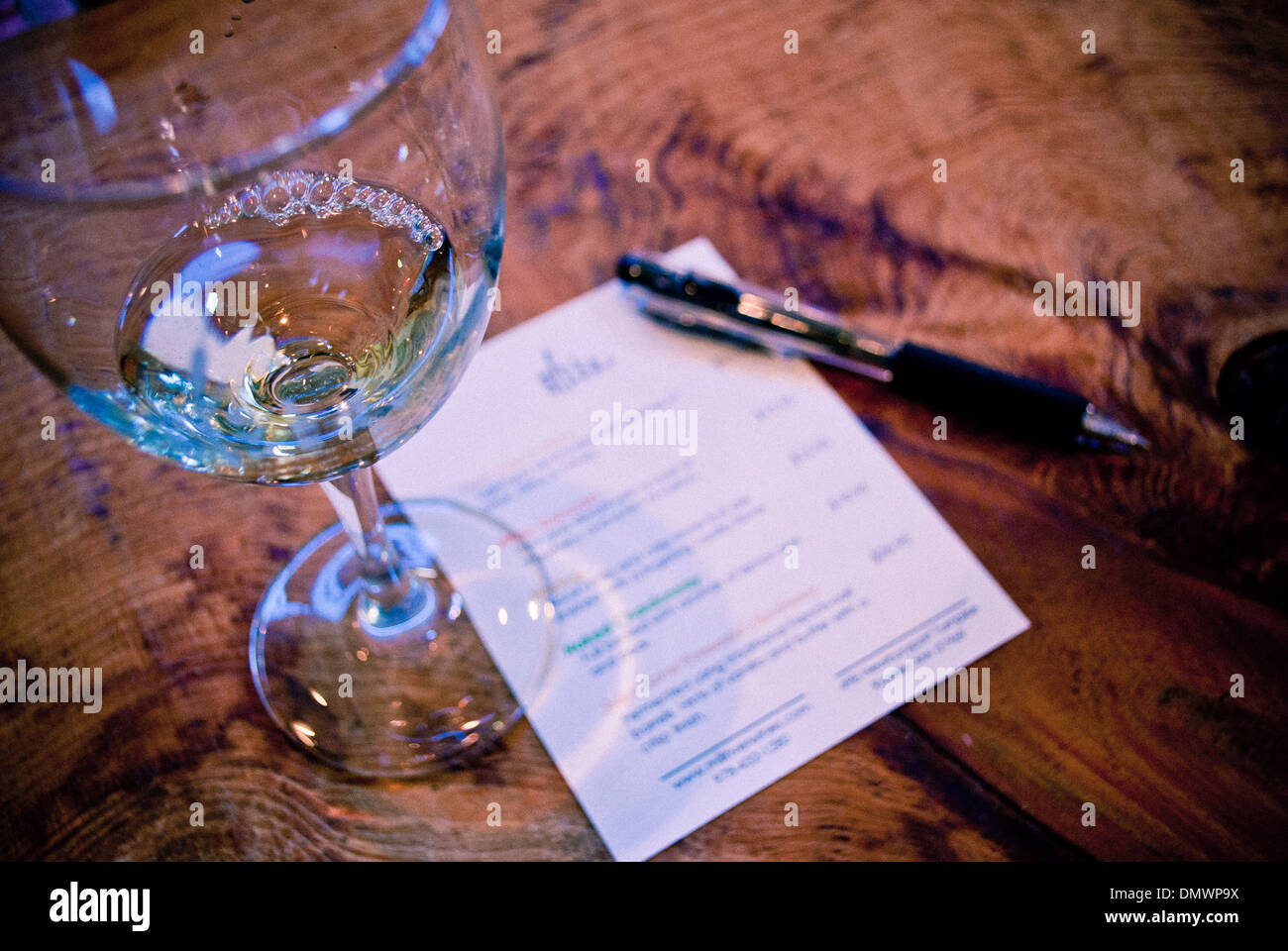 At the wine tasting: glass of wine, sheet of paper and a pen. - Stock Image