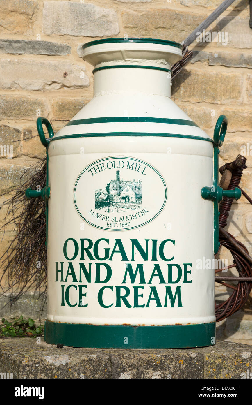 An old milk churn painted to advertise ice cream at the Old Mill Lower Slaughter the Cotswolds UK Stock Photo