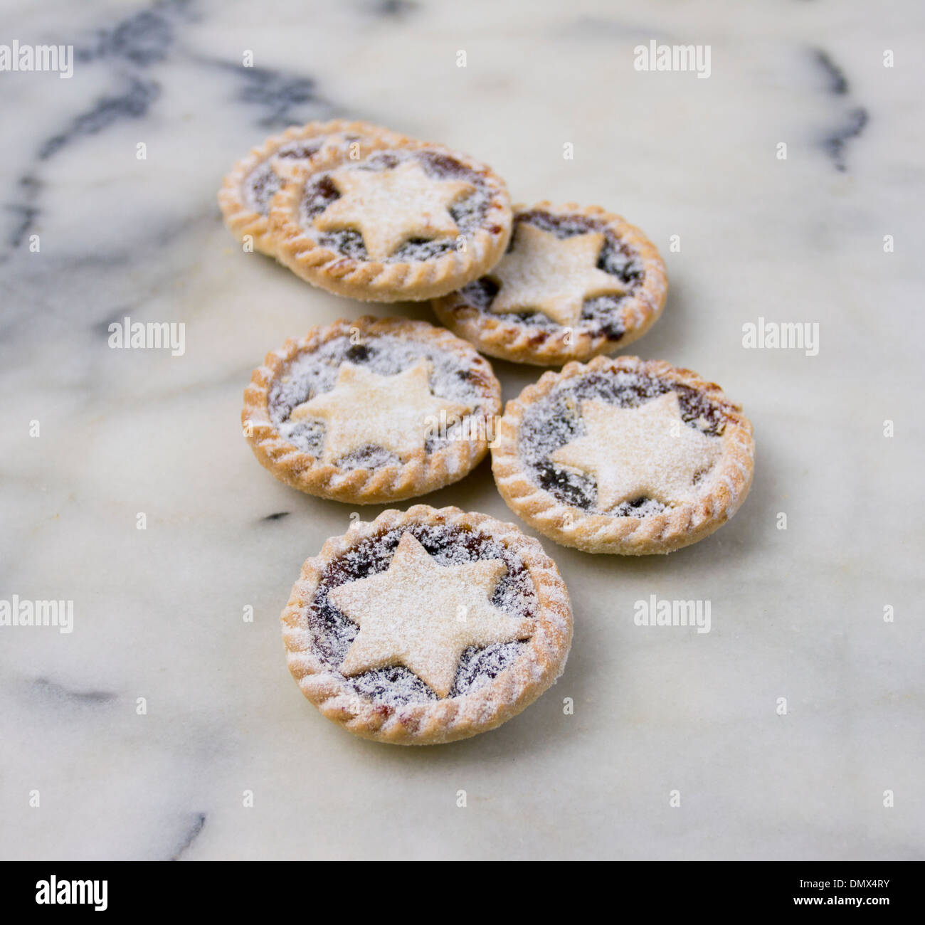 Six home made icing sugar dusted mince pies on grey marble surface - Stock Image