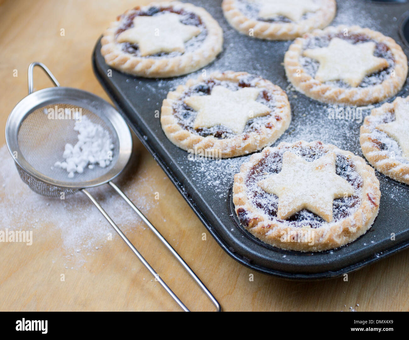 Home made icing sugar dusted mince pies in baking tray with sieve on wooden surface - Stock Image